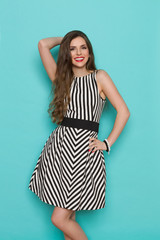 Smiling attractive young woman in black and white striped dress posing with hand on hip and looking at camera,