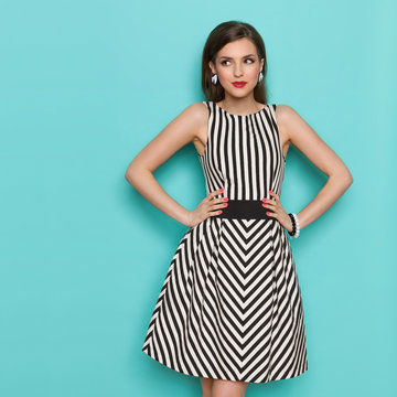 Smiling elegant woman in black and white striped dress posing with hands on hip and looking away,