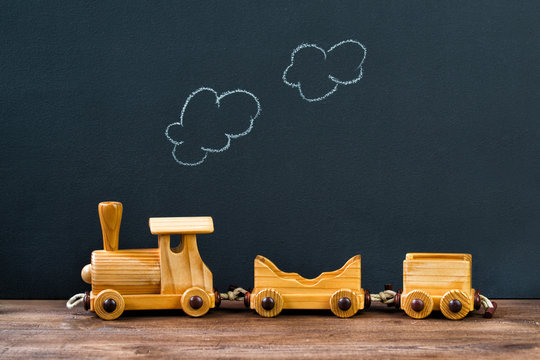 Old wooden toy train with steam on the chalkboard background
