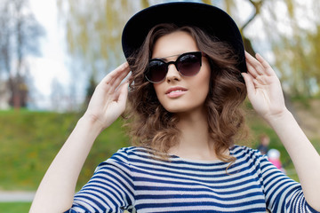 portrait of a beautiful cute young smiling girl in a black hat and sunglasses in an urban style
