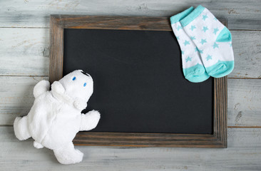 Empty chalkboard with frame, decorated with toy white bear and little white and baby socks on wooden background