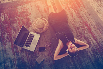 Young woman in dress resting and listening music with headphones. Intentional sun glare and vintage color