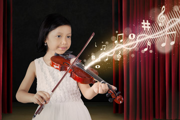 Female child playing violin on stage