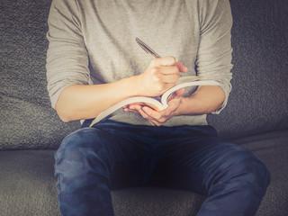 Man writing on book, sitting on sofa, vintage filter