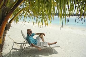 bald  man on a sun lounger under a palm tree in the Maldivian b