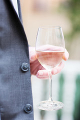 Person holding a half full glass of wine