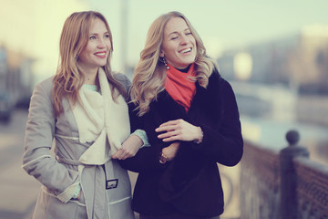 two cheerful blonde for a walk in the city