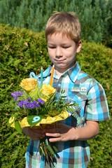 Junge betrachtet Blumenstrauß zum Schulanfang mit Stiften und Zahlen