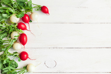 white and red radishes on a white wooden background, flat lay, top view