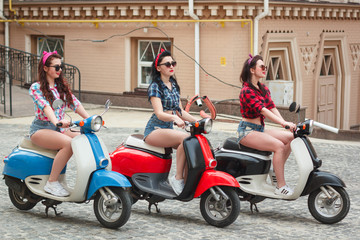 Three sexy young woman on scooter