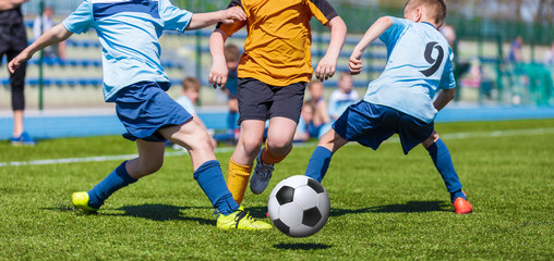 Young boys kids kicking soccer football on the sports field. Football match for children. Training and football soccer tournament.