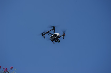 white drone hovering in blue sky