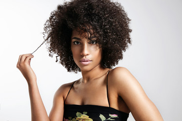 pretty woman with curly afro hair touch a part of it