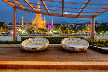 Relax corner on condominium rooftop garden with chairs on landmark bangkok Wat Arun at night background, Landmark concept