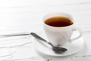 Tasse Tee auf weißem Hintergrund aus Holz.