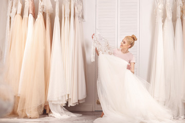Attractive young woman is selecting bridal gown