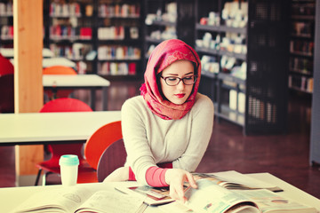 Muslim girl at the library with book