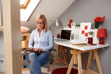 Young woman using tablet at home