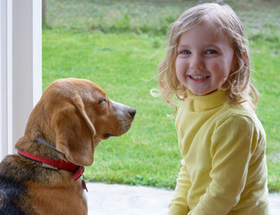Young cute girl with dog playing in garden
