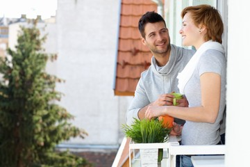 Happy young couple standing at balcony