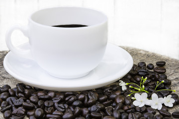 Coffee in white cup with coffee beans on wood table