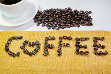coffee by coffee beans with black coffee in white cup