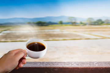 black coffee in white cup with hand holding