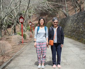 Senior mother and adult daughter standing on the road at Nishikyo-ku, Kyoto, Japan.