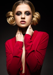 Beautiful girl in a red dress with a deep neckline and black rings on his fingers. The model with bright makeup. Was was made in the studio.