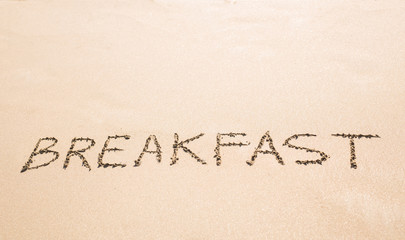 The Word Breakfast Written on the Sand at a Beach