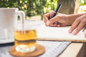 Writing outdoor in the garden with cup of tea
