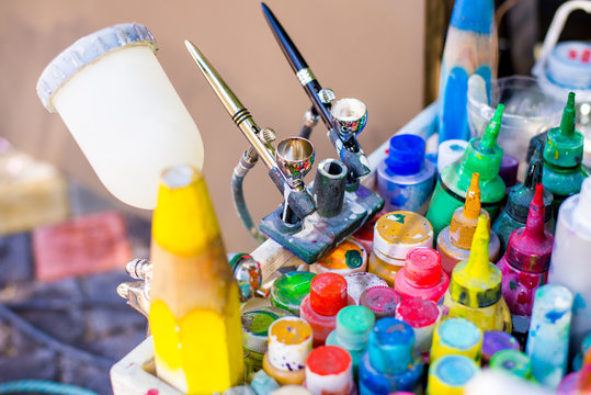 Professional airbrush on a stand with colorful paints in backgroung