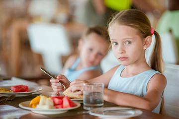 Adorable little girls having breakfast at resort restaurant