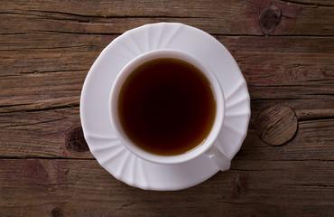 Tasse Tee auf braunem Hintergrund aus Holz - Ansicht von oben.