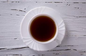 Tasse Tee auf weißem Hintergrund aus Holz - Ansicht von oben.