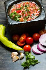 Tomato sauce salsa and ingredients dark stone background.