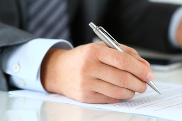 Close up of businessman hands signing documents