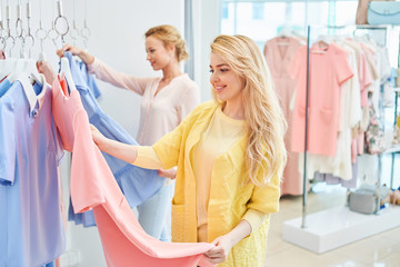 Two girls looking at clothes on hanger in clothing store