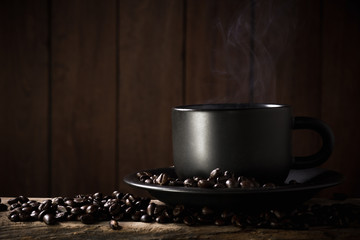 Coffee cup and coffee beans on a wood background.