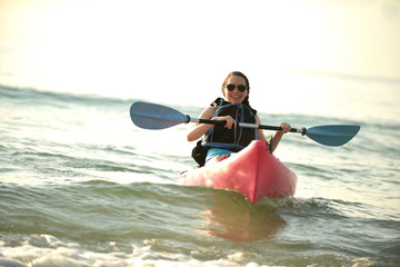 Pretty young woman kayaking in ocean