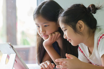 Close up of Asian child using tablet together