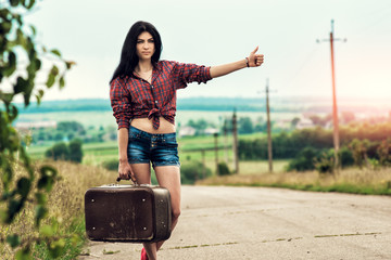 Girl with retro suitcase standing on hitchhiking