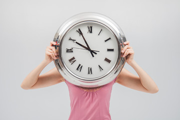 woman holding a clock against a white background