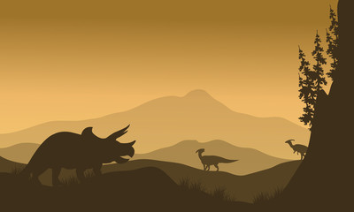 Parasaurolophus and Triceratops in hills of silhouette