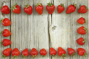 Square shot. Strawberry frame on wooden background, free space for your text.