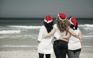 Three beautiful women wearing christmas hat walking on the seasi