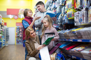 Parents and kids buying writing materials