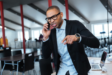 Angry businessman talking on the smartphone
