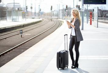 Blonde Frau mit Gepäck und Smartphone auf Bahnsteig,