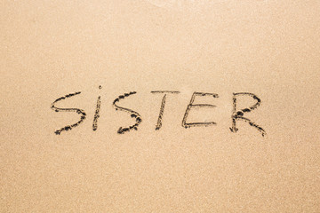 Sister word handwritten on a sand of beach